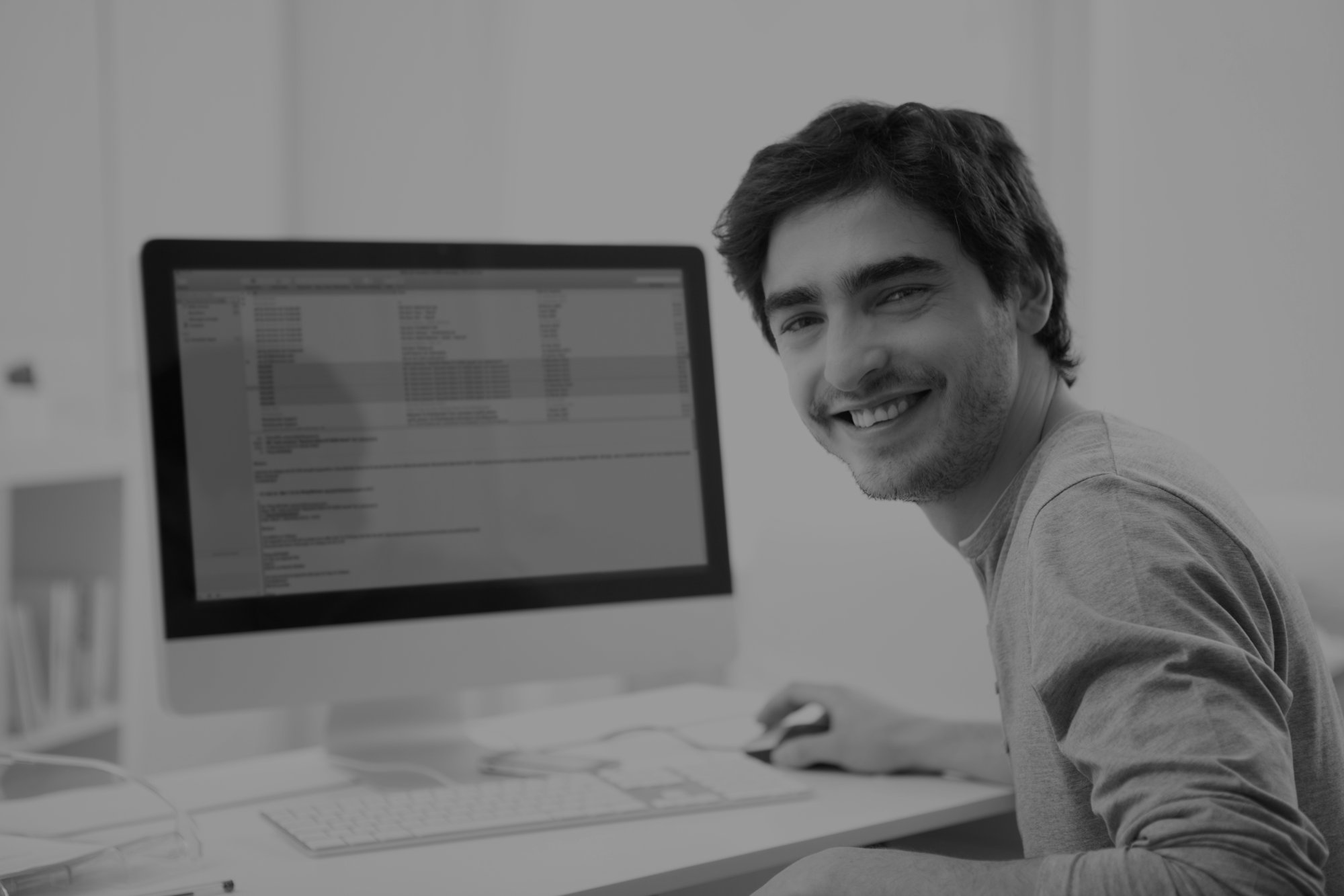 External Lottery Manager - View of a Young smiling man in front of computer